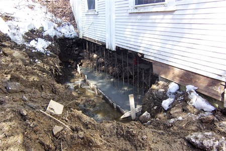On Monday of week 2, a large hunk of the granite foundation was removed and cement footings were installed.