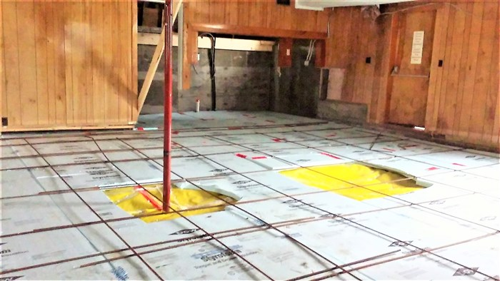 The floor has been prepped for pouring the slab.  The yellow squares are the vapor barrier with insulation and rebars across the top for stabilization.