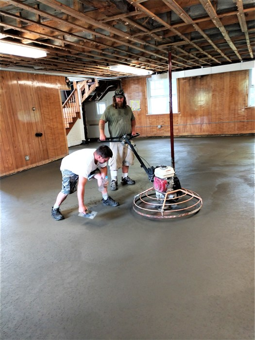 Eric and Walter complete the pouring of the slab.  We now have a floor in the basement once again.